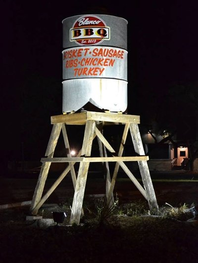 A small watertower at night located at Blanco BBQ