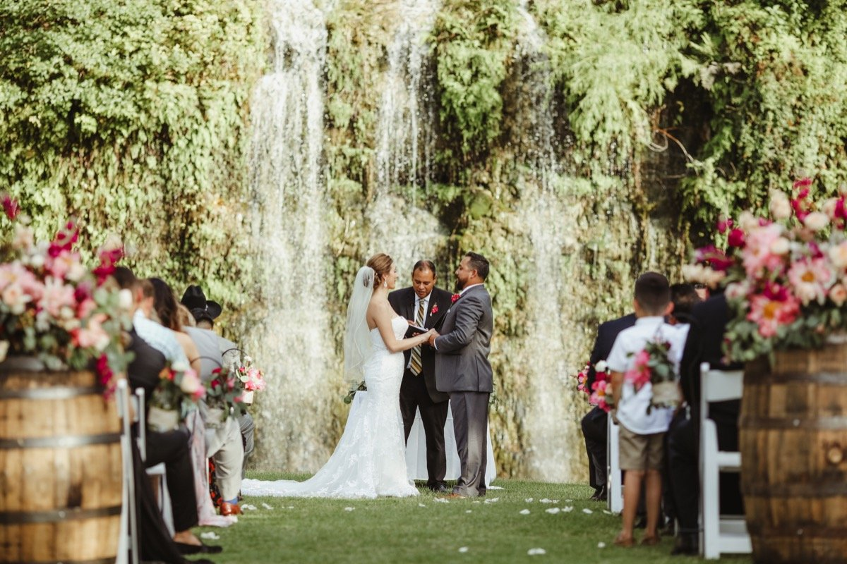 A woman takes her husband in front of everyone near the waterfall at the Canyon Springs Golf Course.