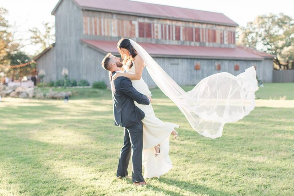 A Bride is lifted into the air by her Groom, with the Eagle Dance Ranch. barn in th background.