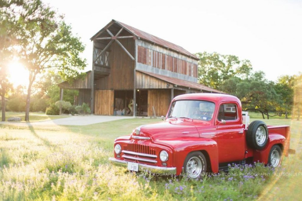 A bright red pick-up truck sits near the Eagle Dance Ranch Big Barn