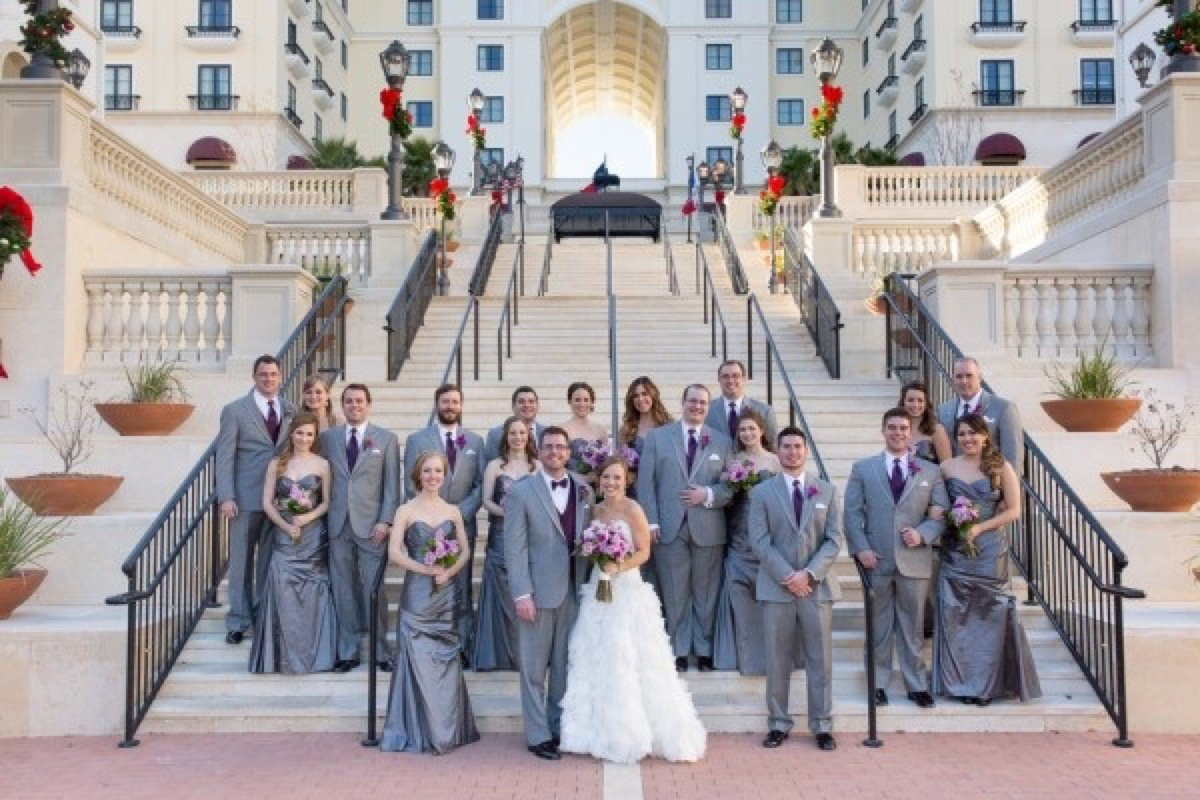 The wdding party and Bride and groom all gathered at the foot of the stairs for a The Eilan Hotel Resort and Spa picture.