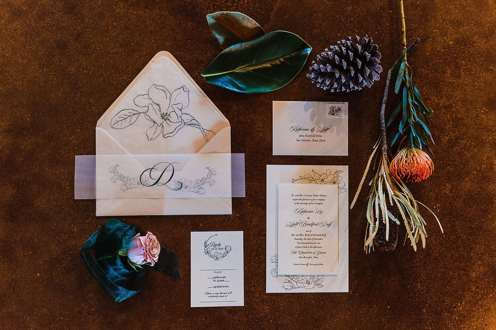 dark tone wedding stationary styled with leaves and pinecones
