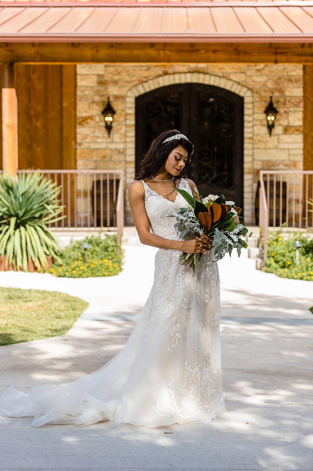 San Antonio bride holding er bouquet striking a pose at chandelier of gruene