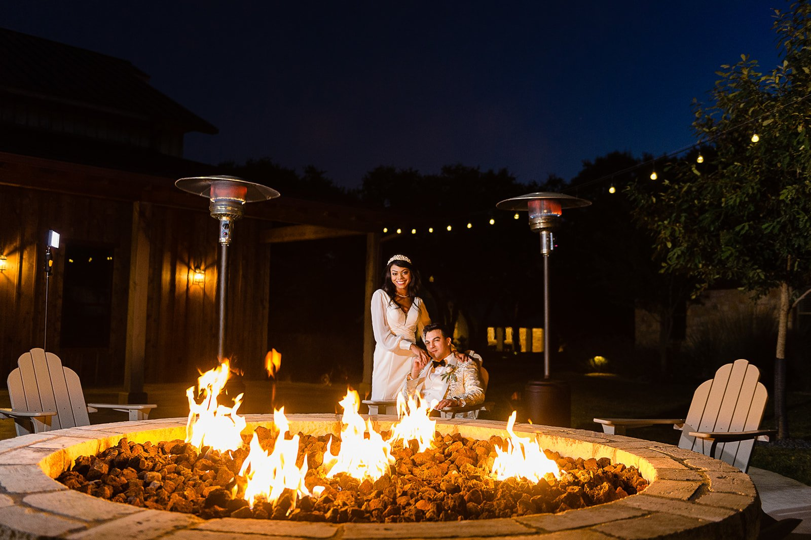 married couple at wedding sitting by firepit