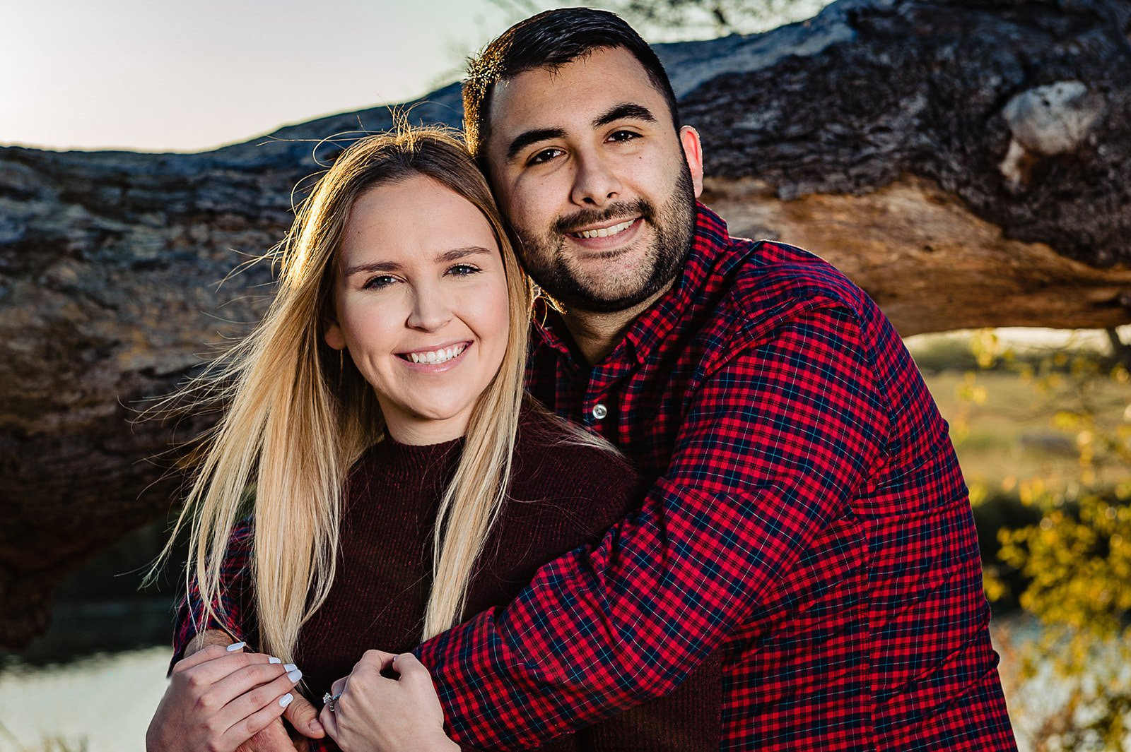 happy engaged couple couple wearing maroon in front of fallen tree