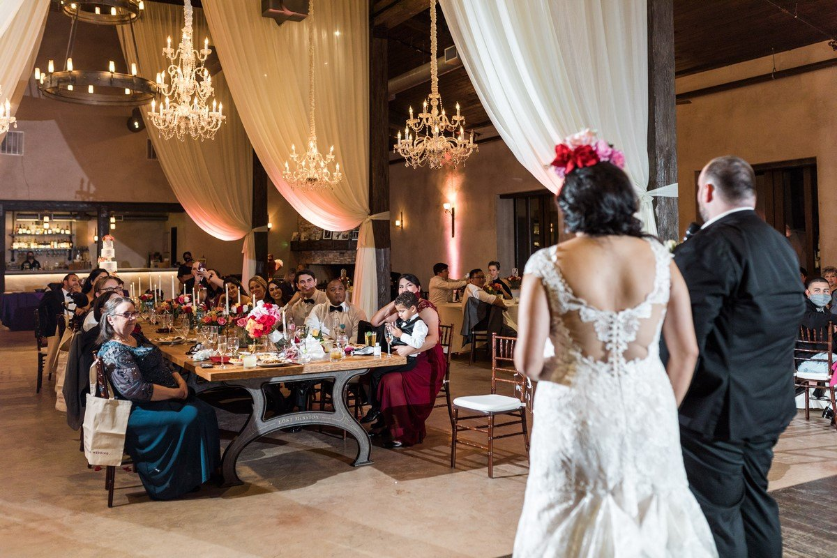 newly wed couple looking at their wedding guests chandeliers and french decor