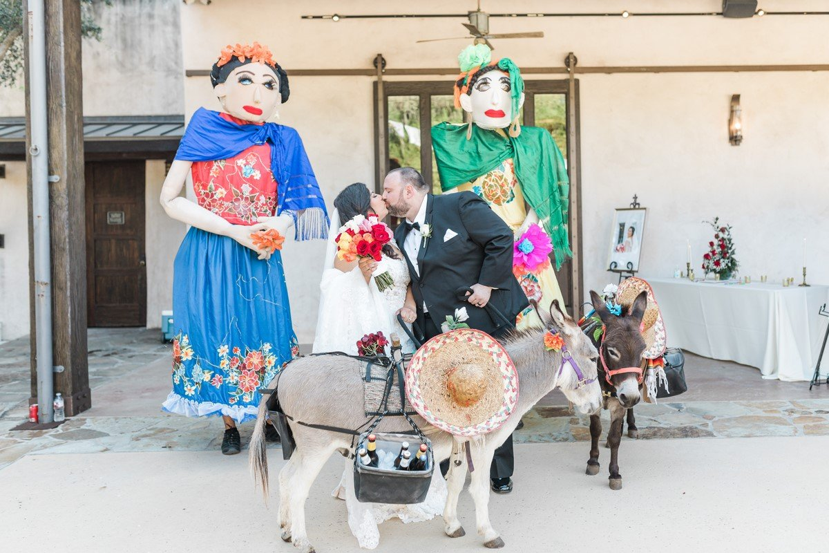 newly wed couple kissing in front of mojigangas and a donkey
