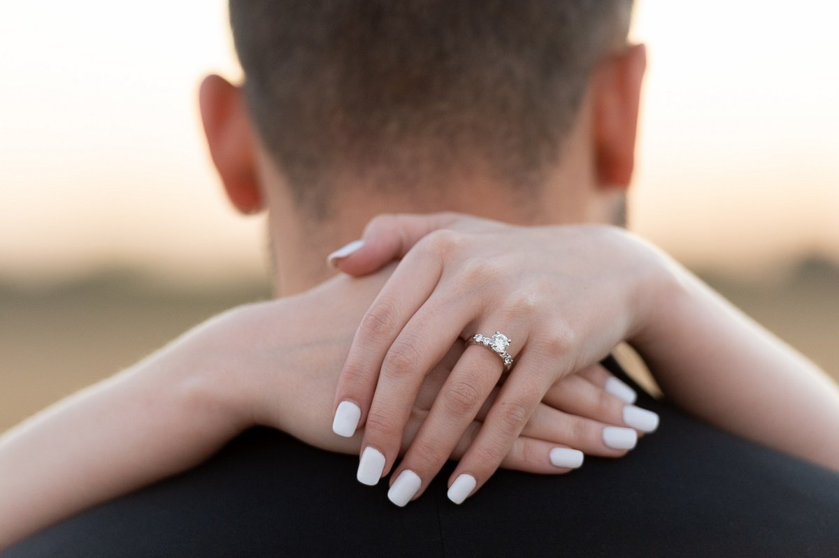 natural lighting engagement photo of ring behind grooms back