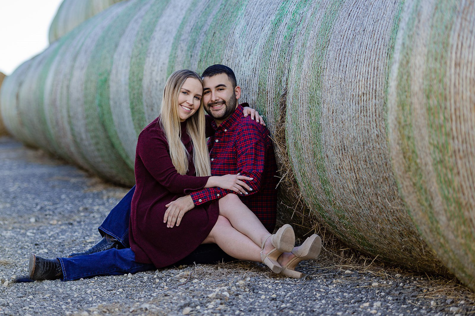 country couple posing for engagement shots in front of hay barrels