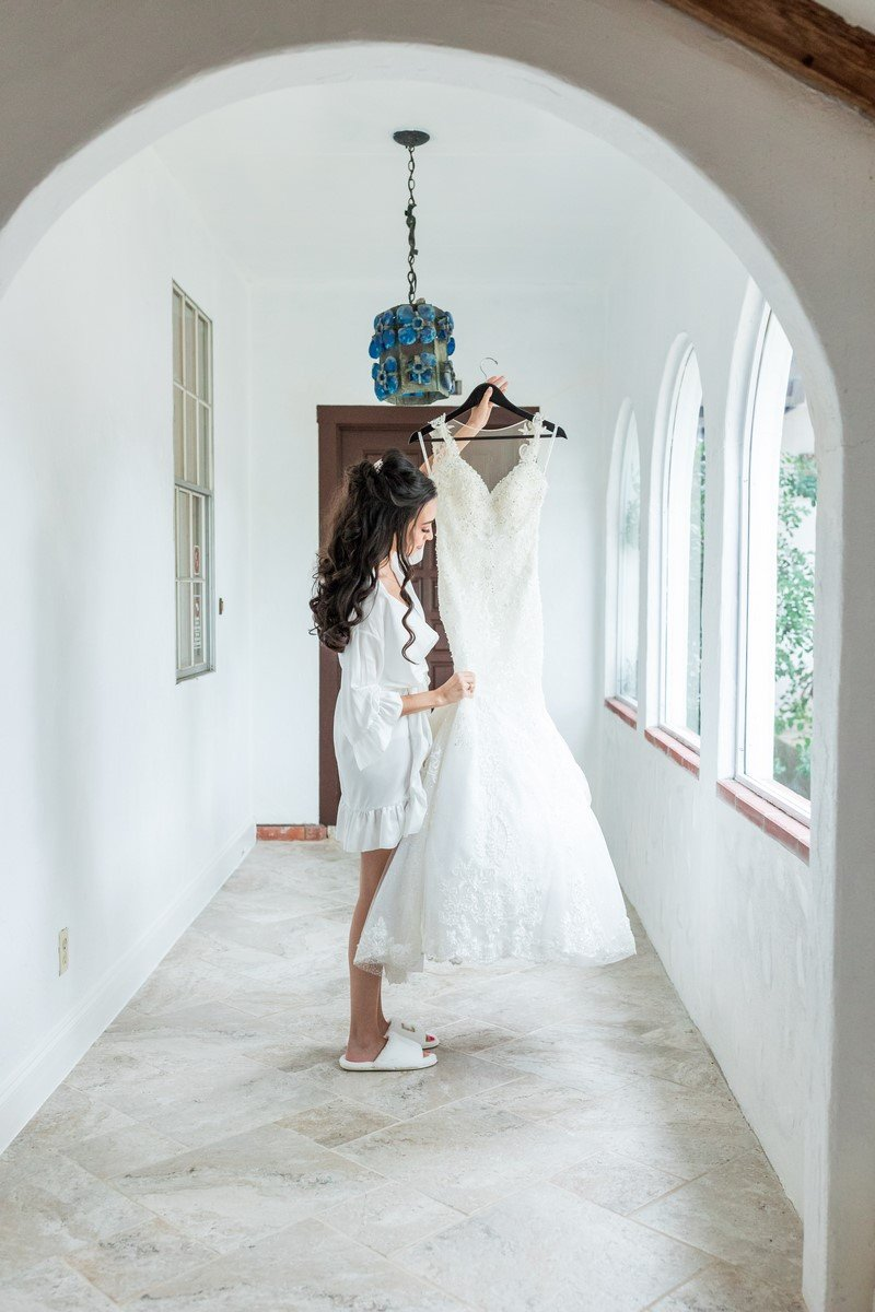 bride holding her dress in a bright and open hallway