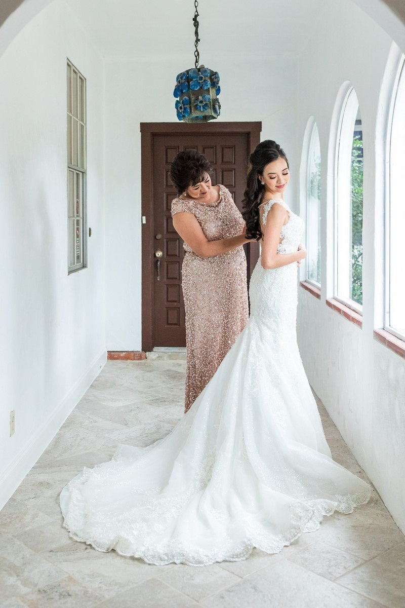 mother of the bride helping her daughter put her wedding dress