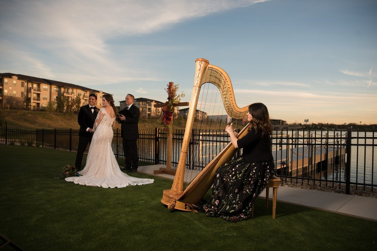Harpist wearing a dress playing for a wedding near a lake at sunset