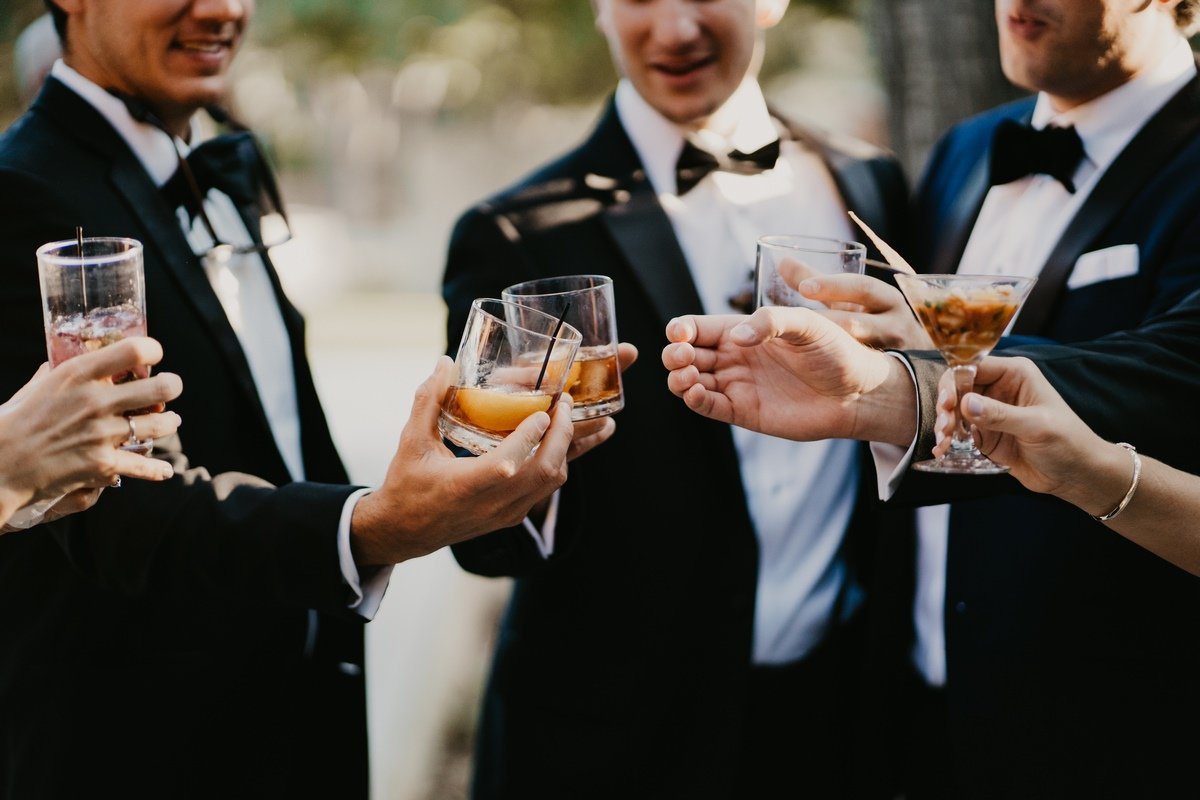 groomsmen saying cheers with their assorted alcoholic beverages