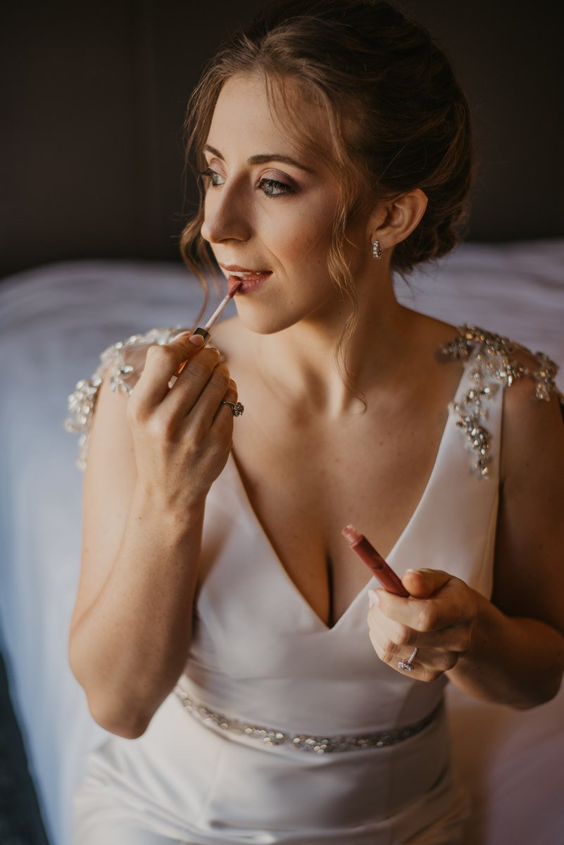 bridal portrait while she is putting on makeup
