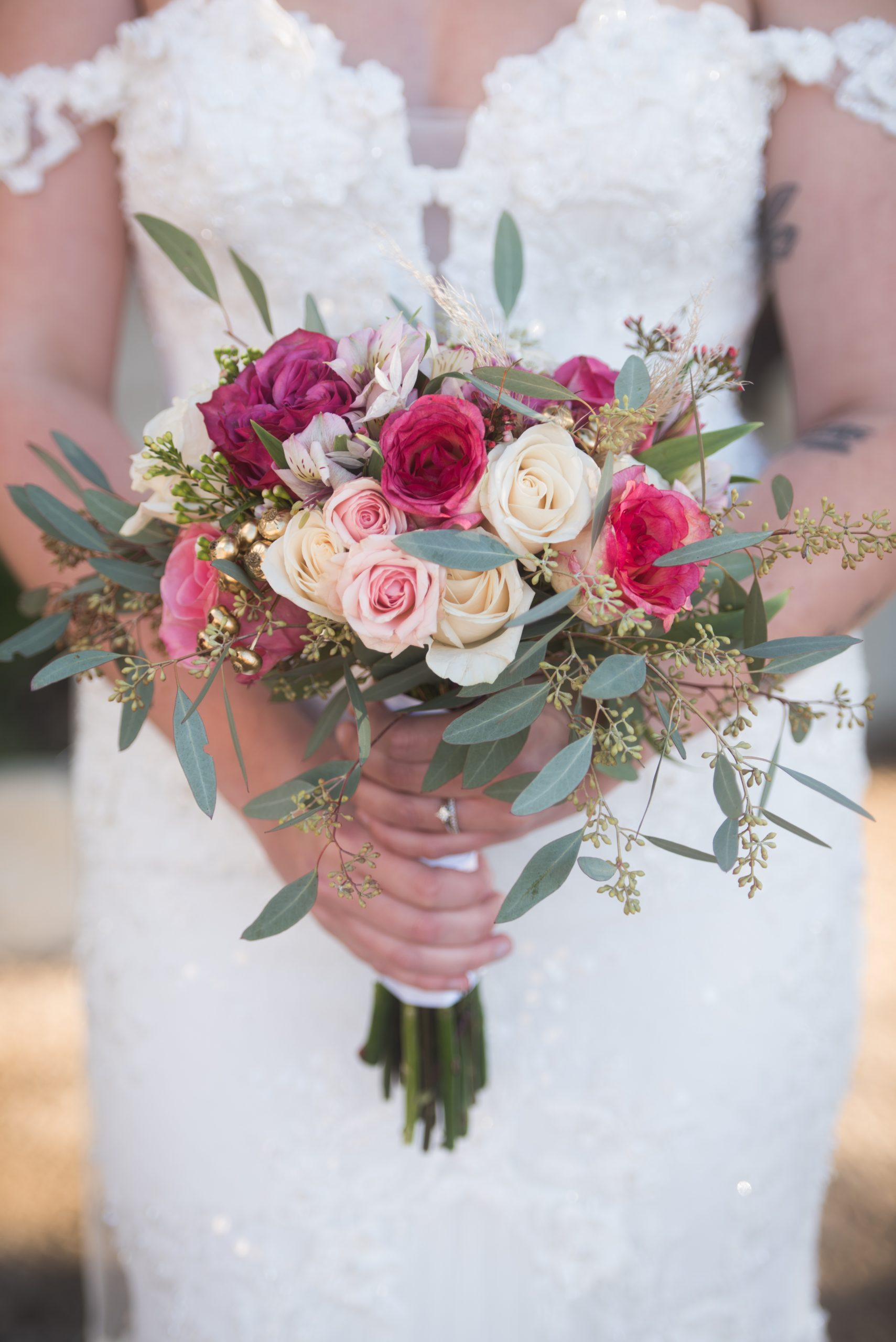 bridal bouquet in front of her wedding dress from bridal connection at Tuscany venue