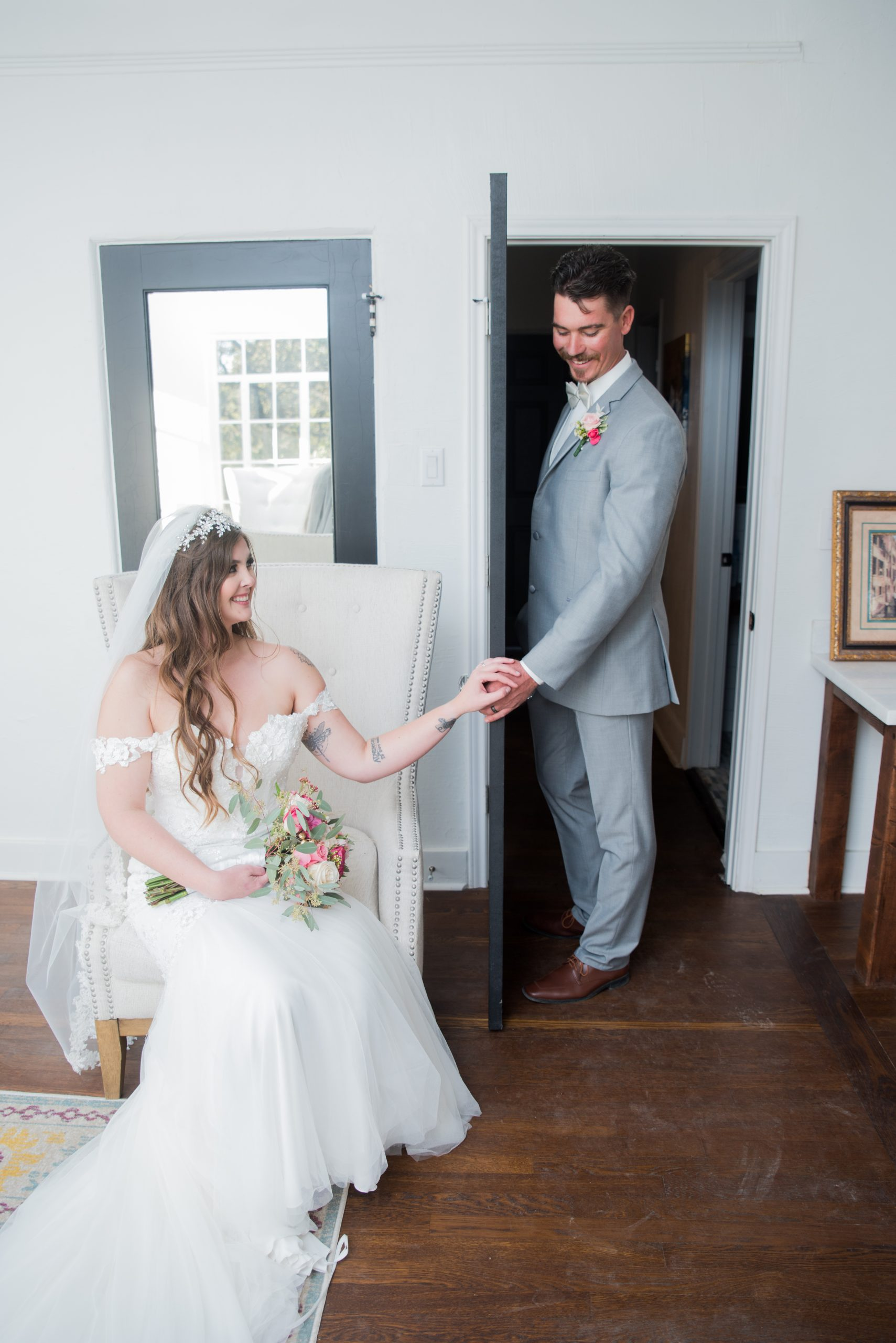 bride and groom holding hands on opposite sides of door but can not see each other