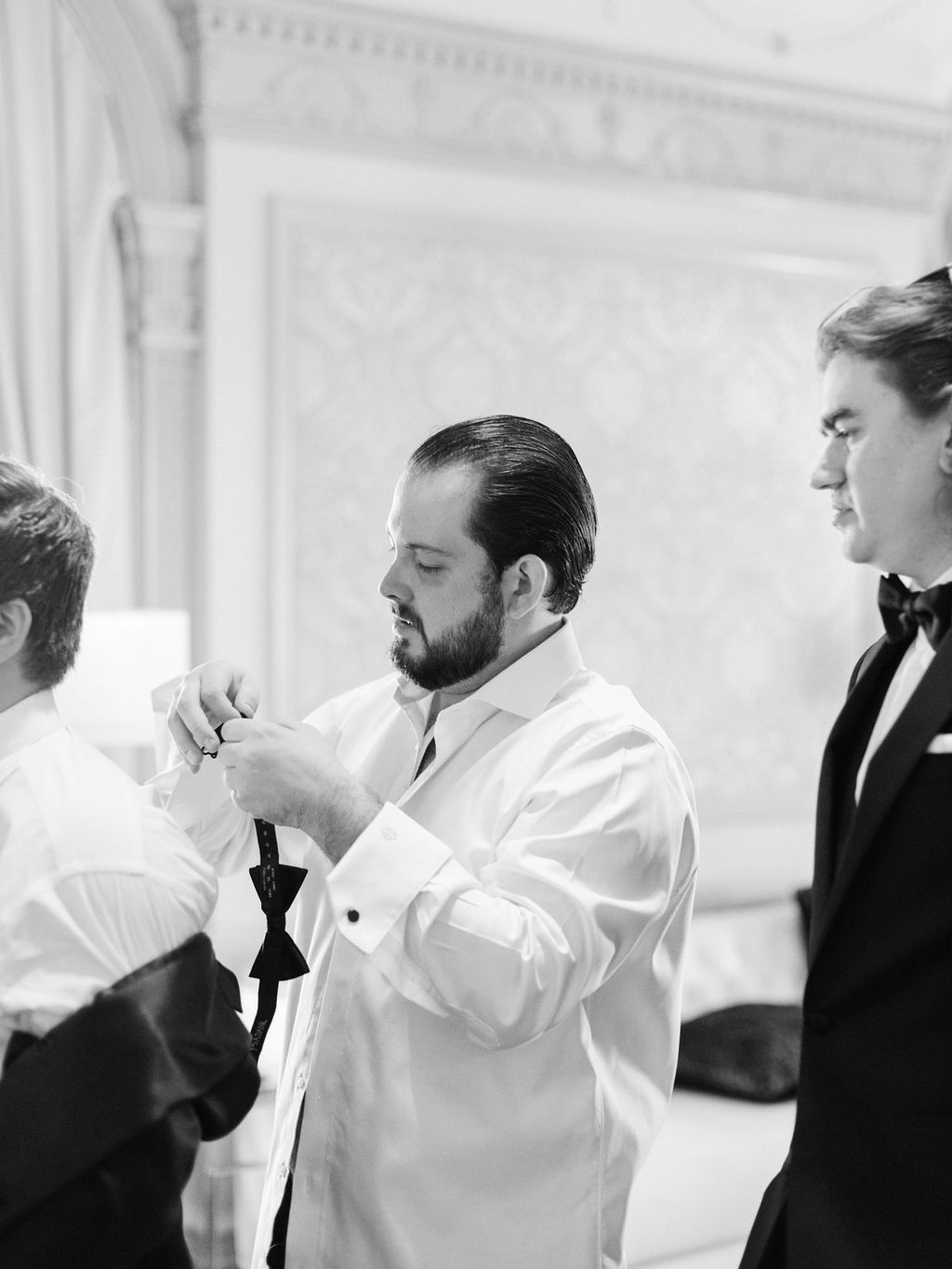 groom with his groomsmen getting ready at the st Anthony hotel