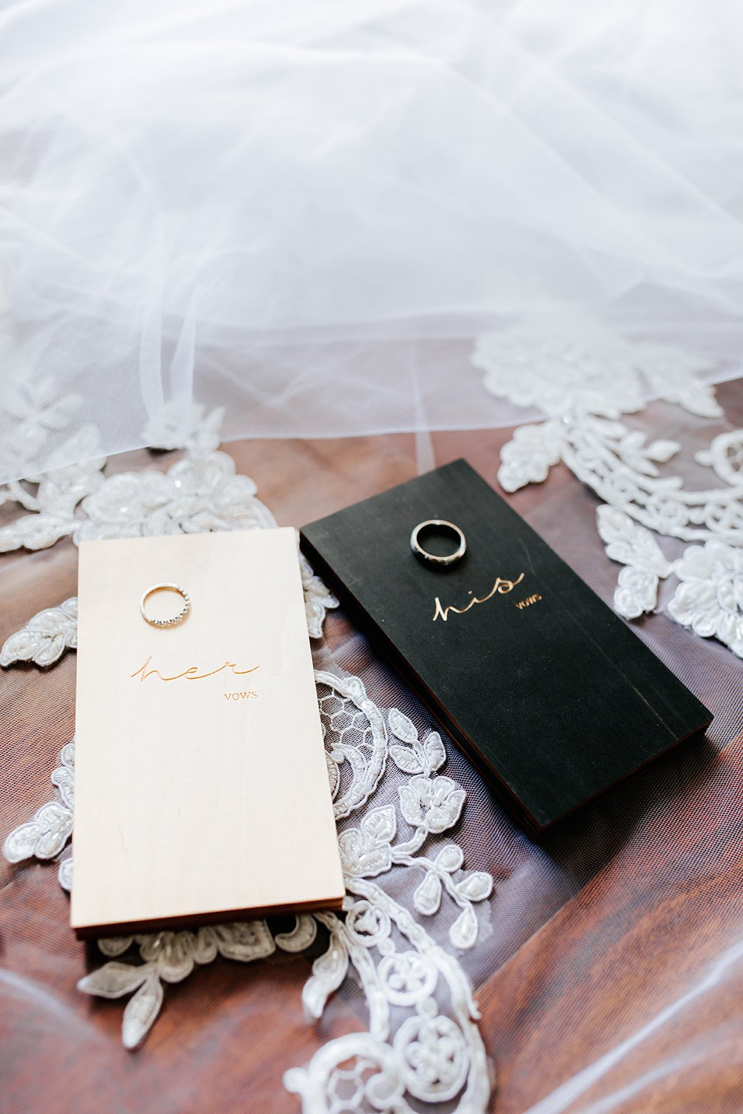 wedding bands sitting on his and hers journals