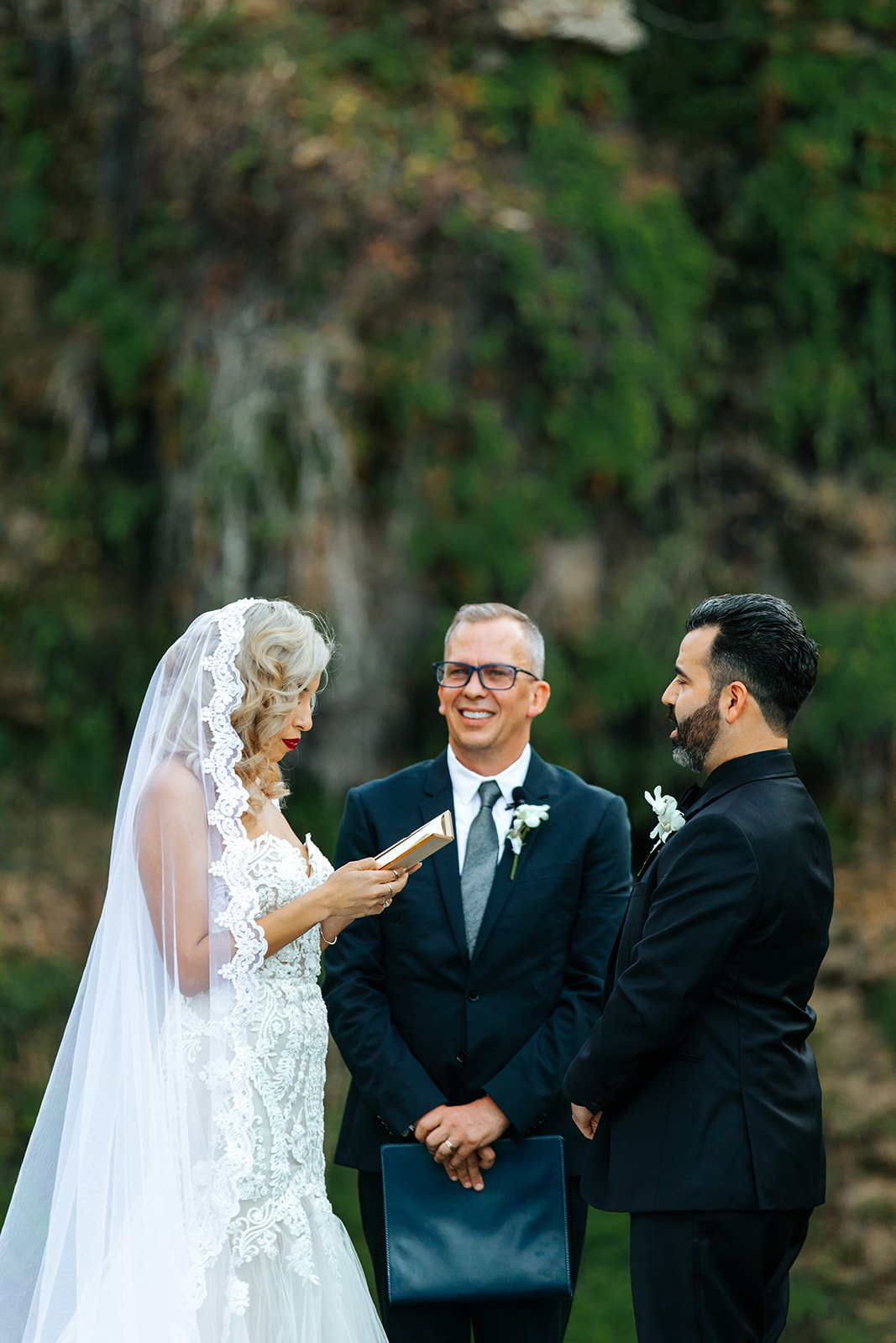 couple saying their vows in front of waterfall