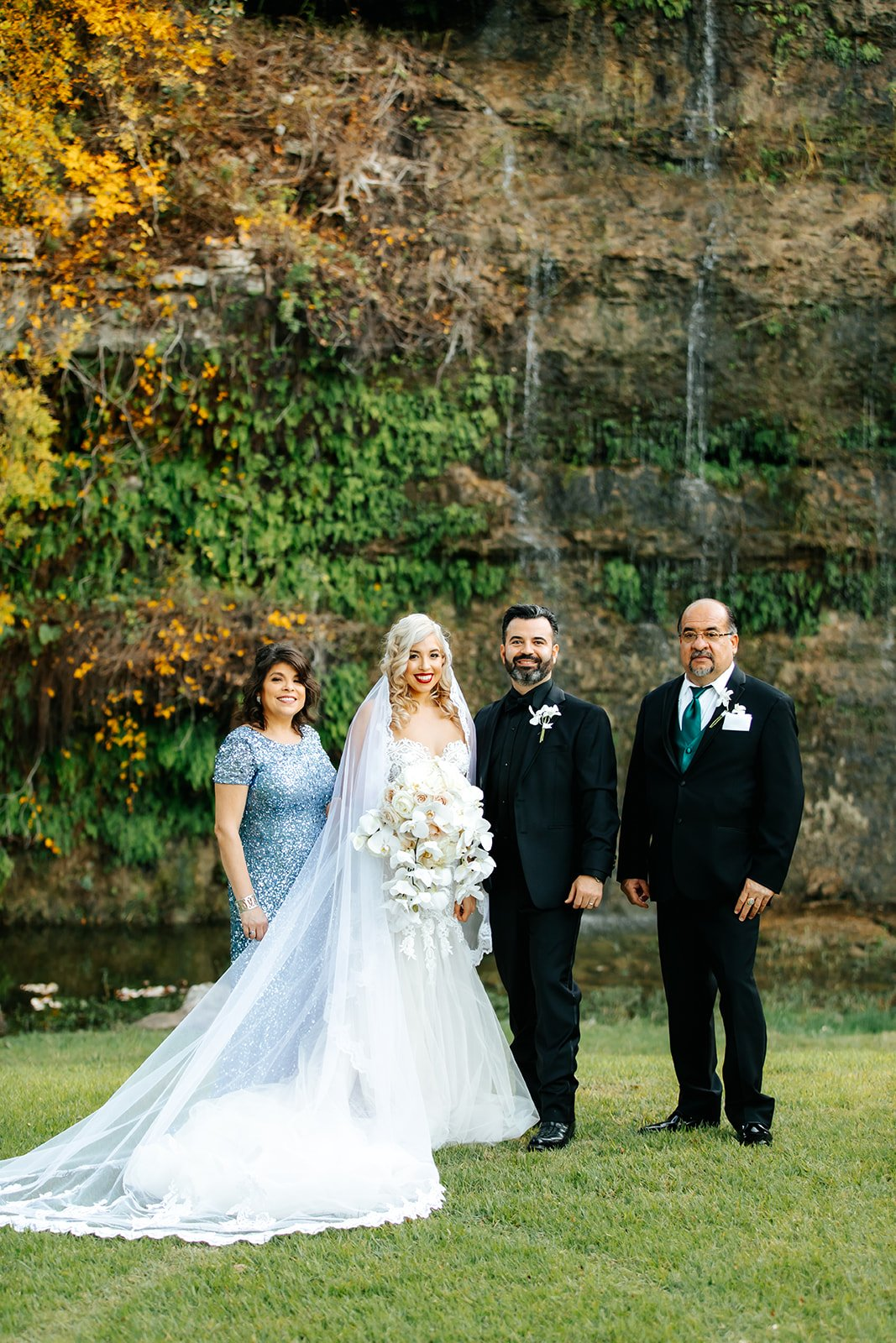 newly wed couple in wedding gown and tux standing in front of waterfall