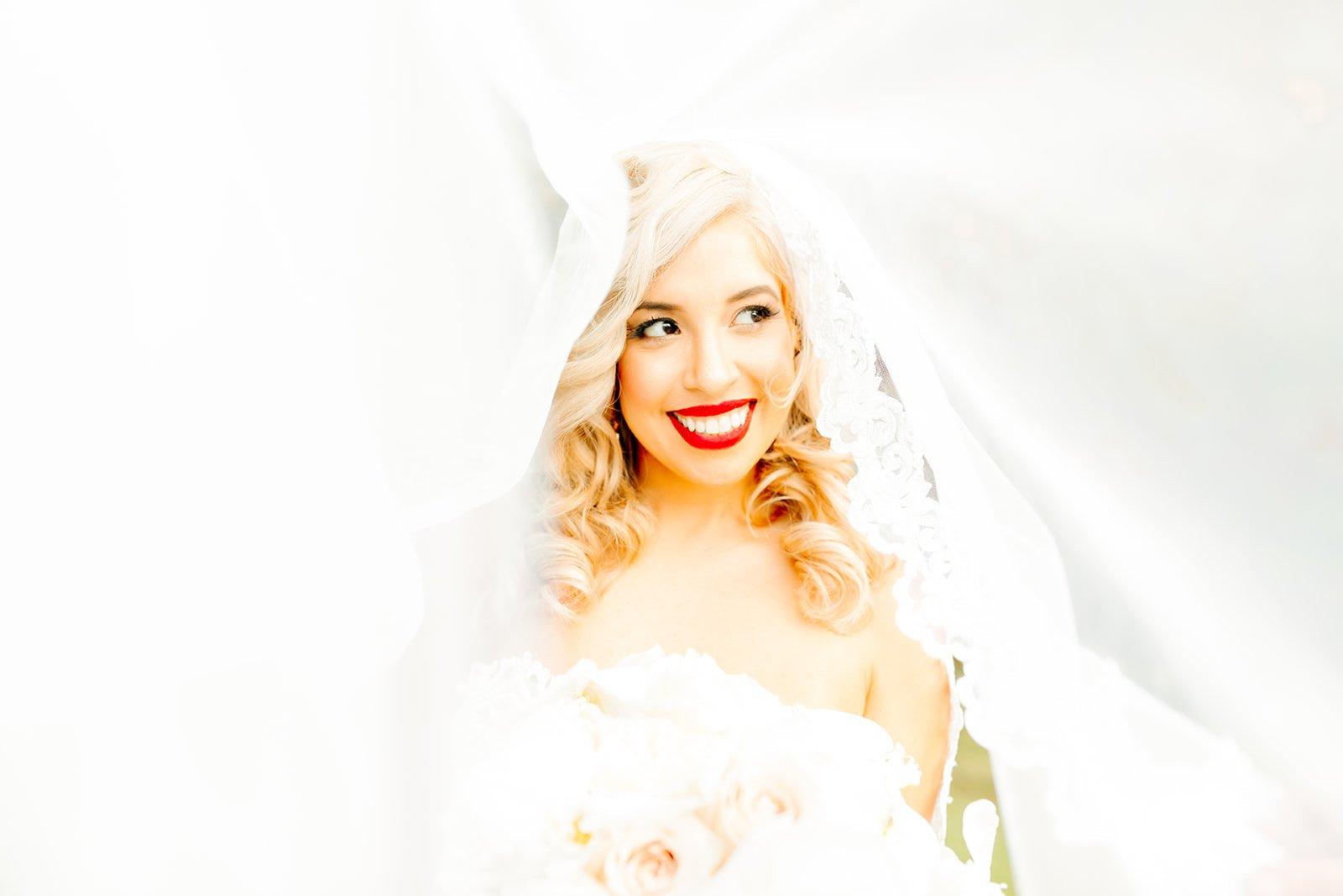 beautiful blonde bride with red lipstick under her veil