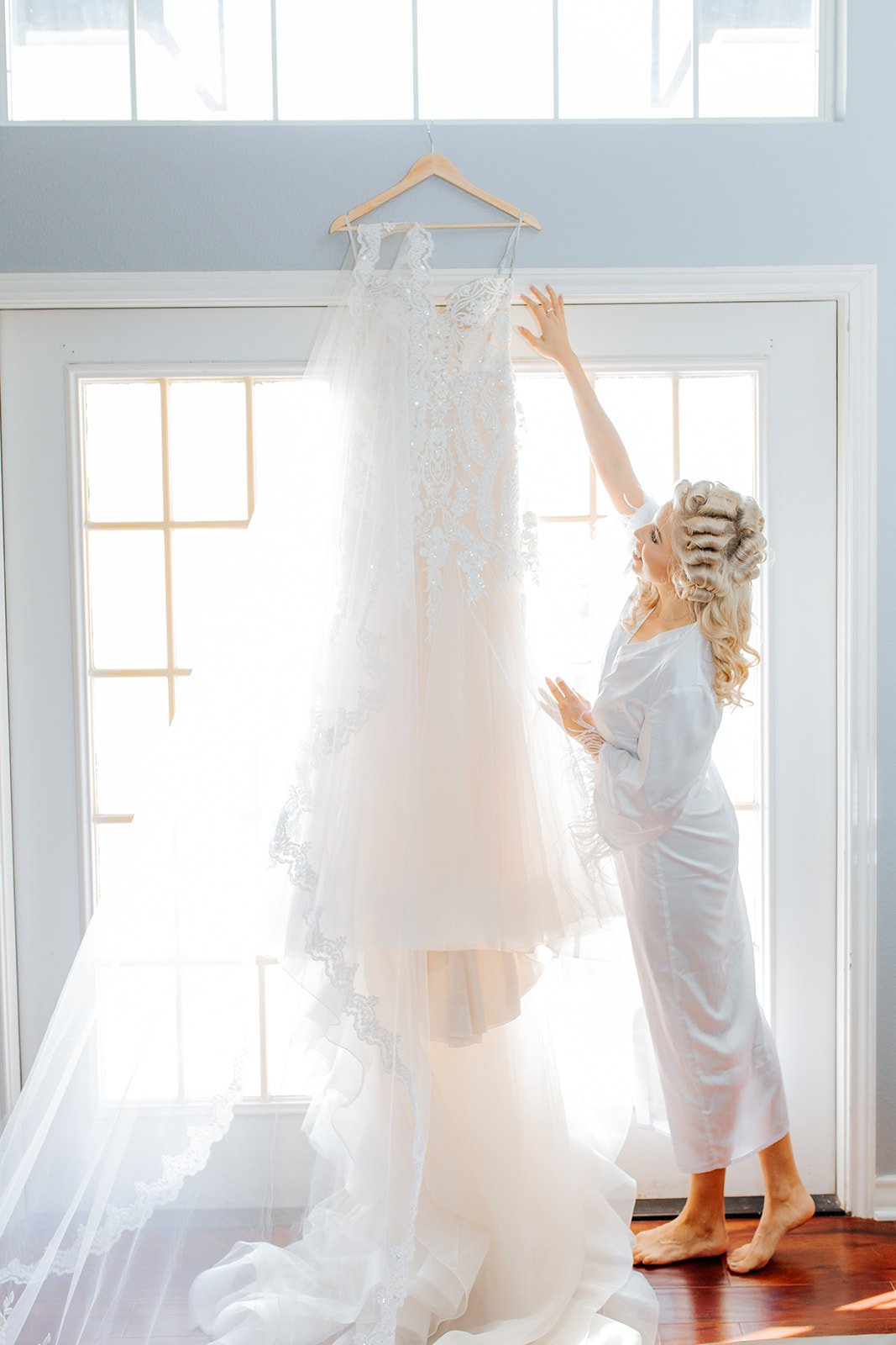 blonde bride getting ready for her big day wedding dress hanging on wall with natural light coming through
