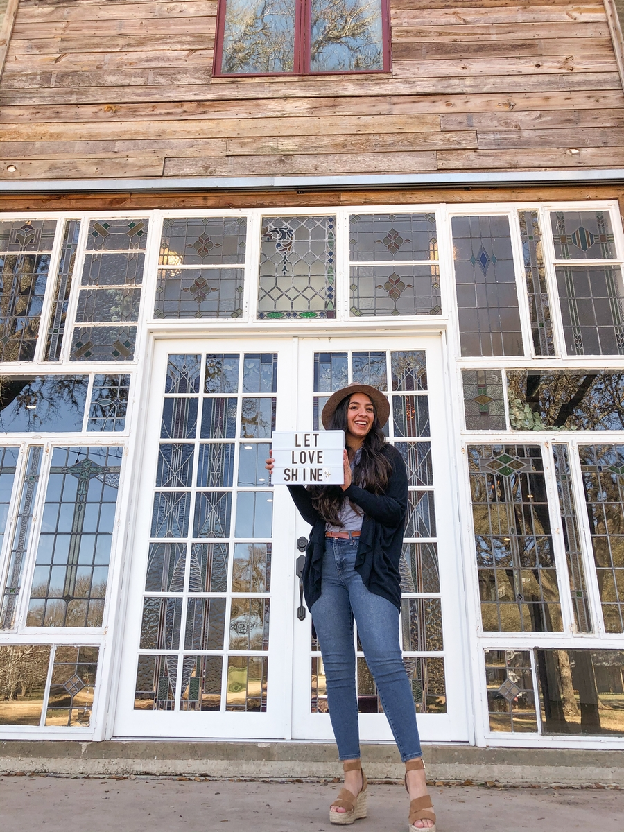 Erika posing in front of Harper Hill Ranch Stained glass windows