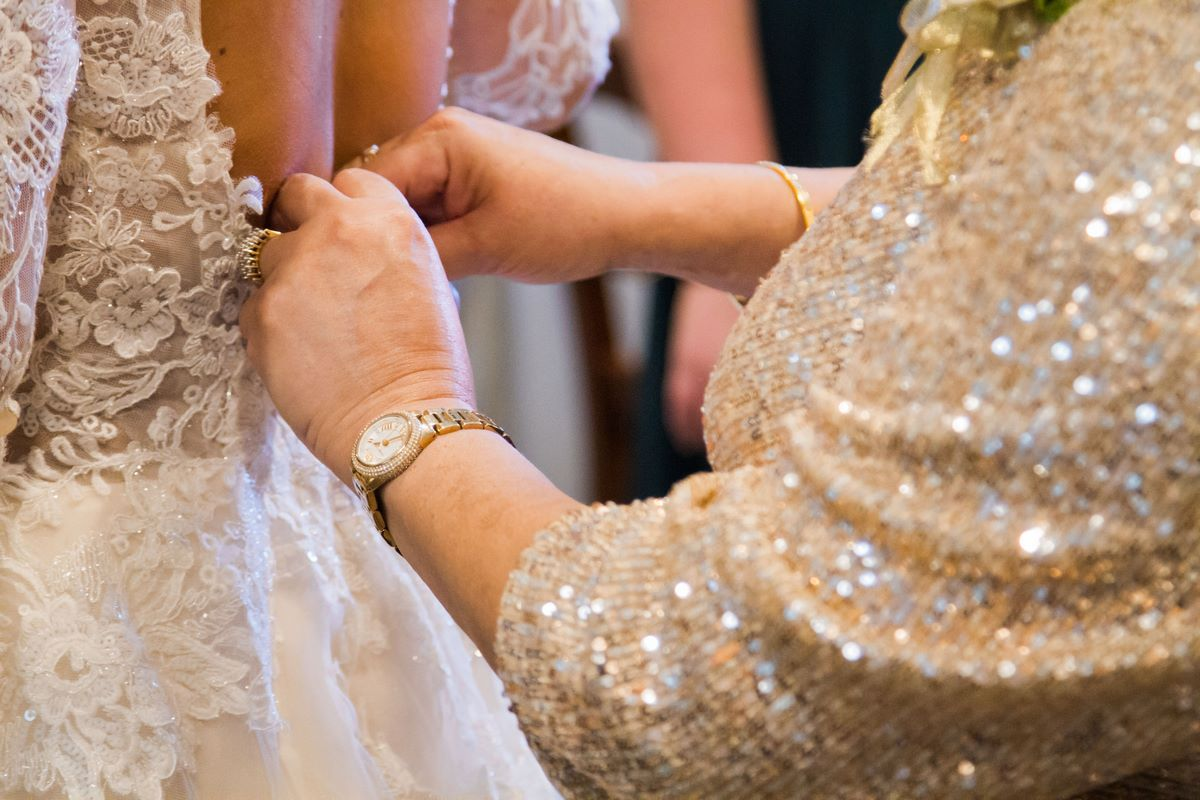 mother of the bride putting on daughters wedding dress