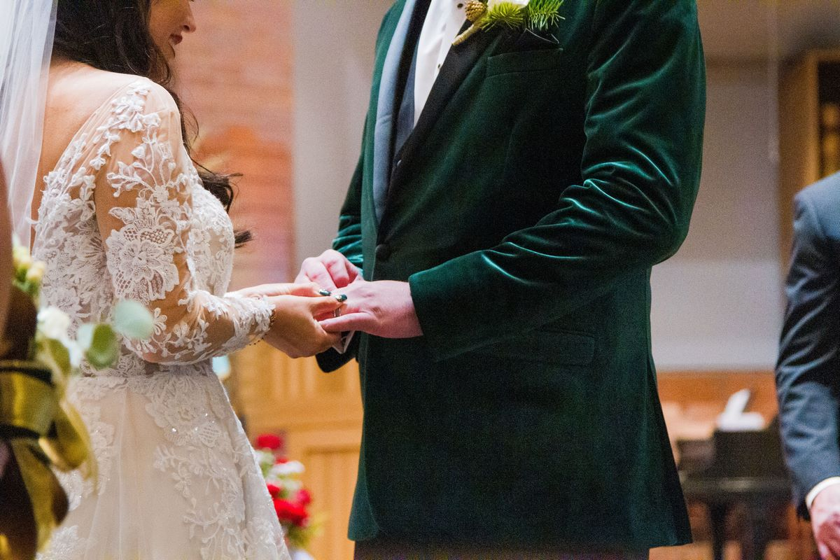 bride putting grooms wedding ring on
