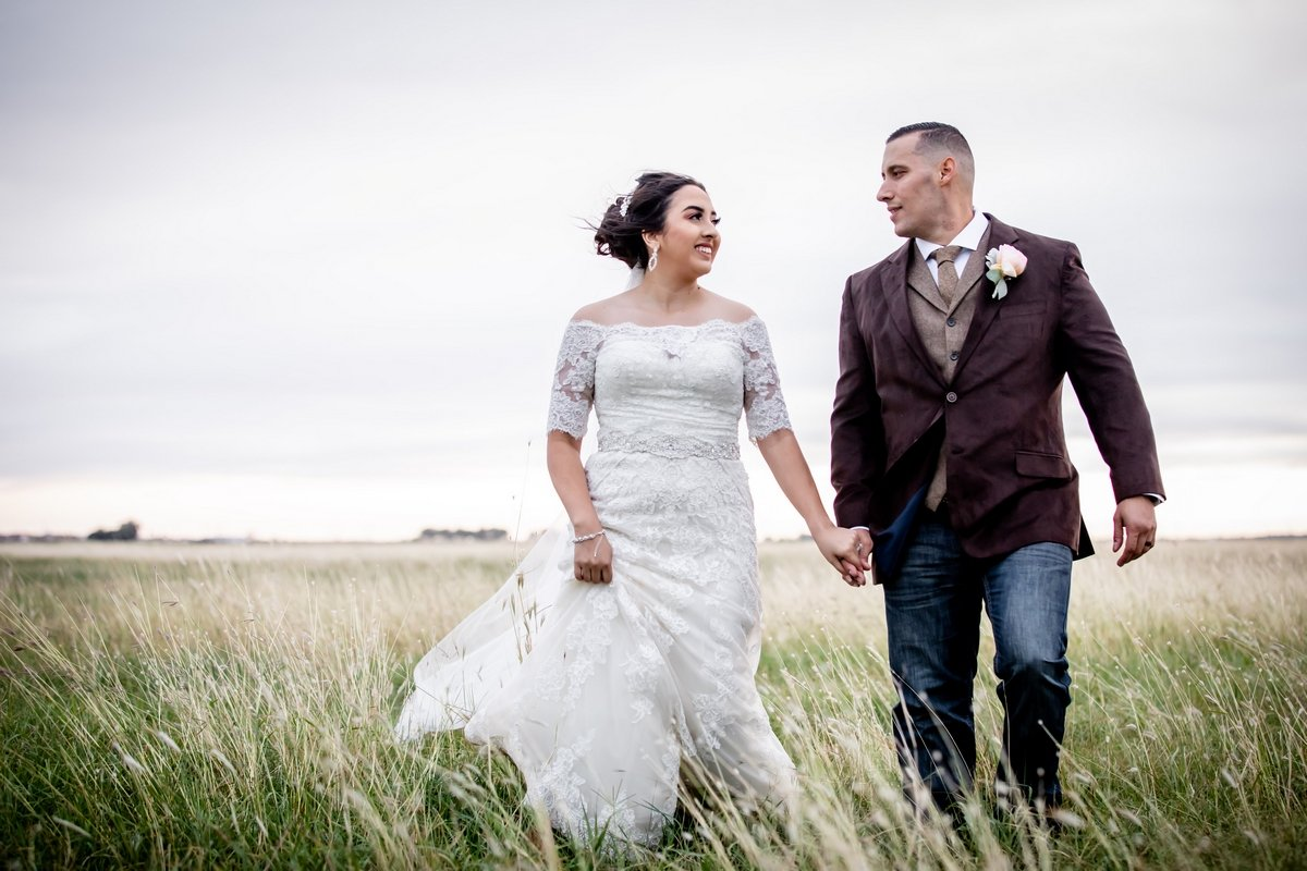 Wedding couple walking through meadow