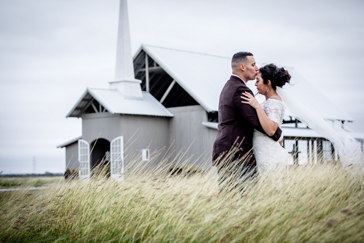 Man and woman embrace in front of wedding venue
