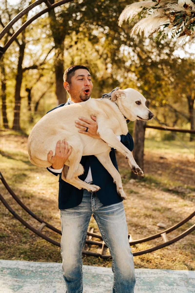 groom holding dog at altar at Harper Hill Ranch