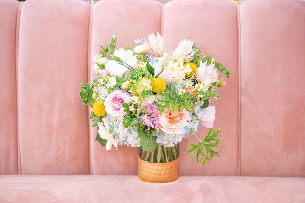pink couch with spring flower bouquet at sendera springs