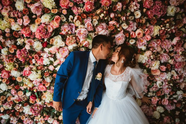 Couple kissing in front of flower wall