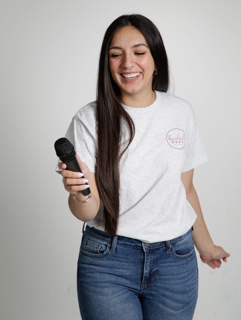 Bridal Buzz Podcast host Erika Perez holding a microphone